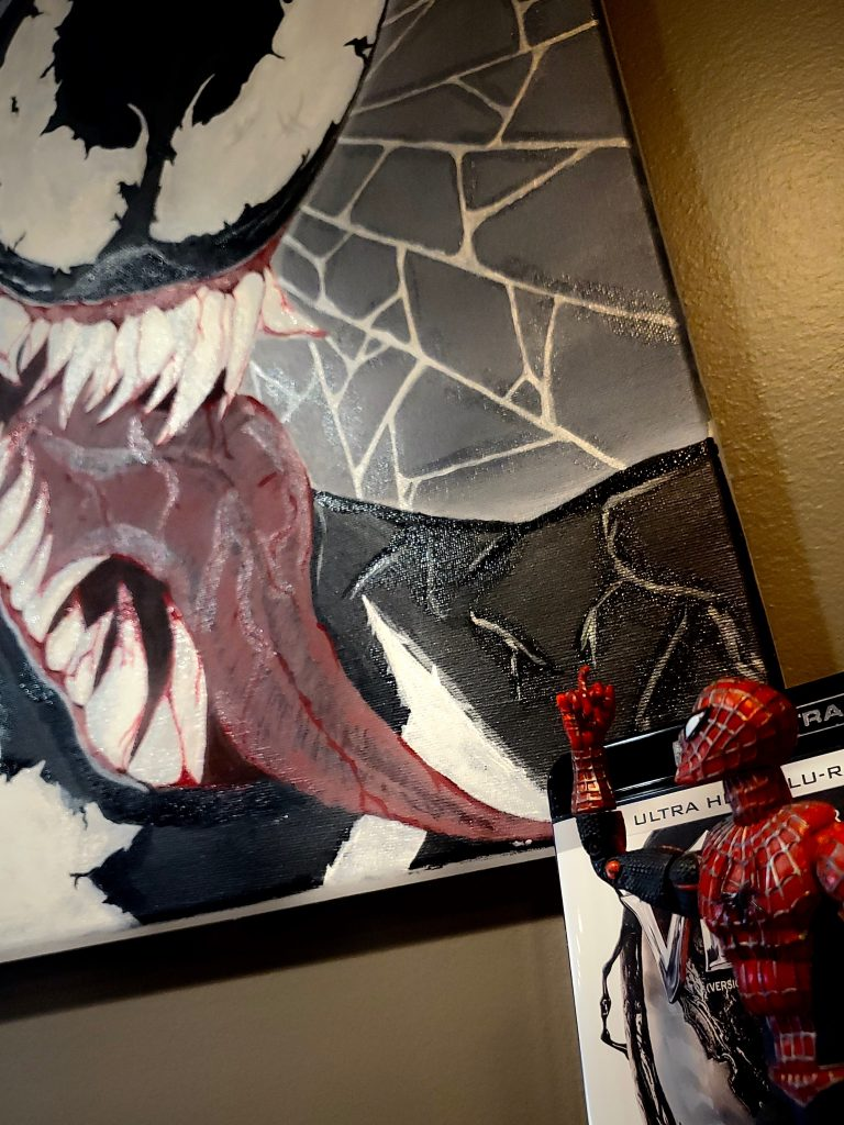 Spider-Man looks onto a painting of his arch-nemisis, Venom.