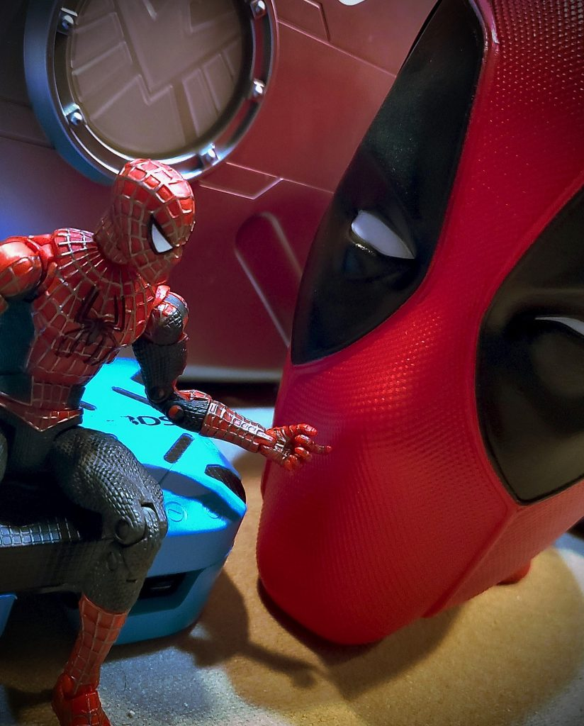 Spider-man toy having a discussion with Deadpool head